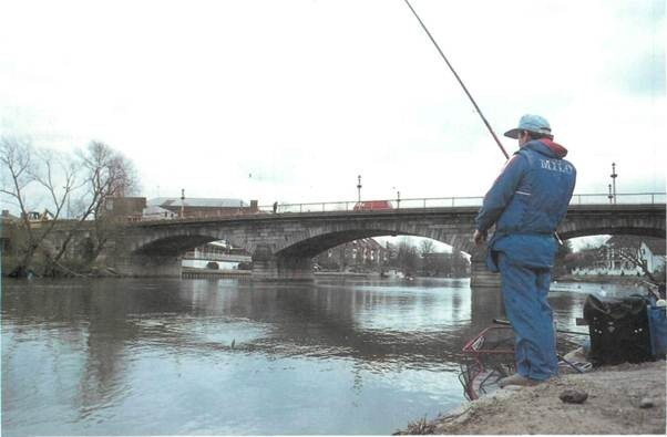 An angler lands a dace from the Thames